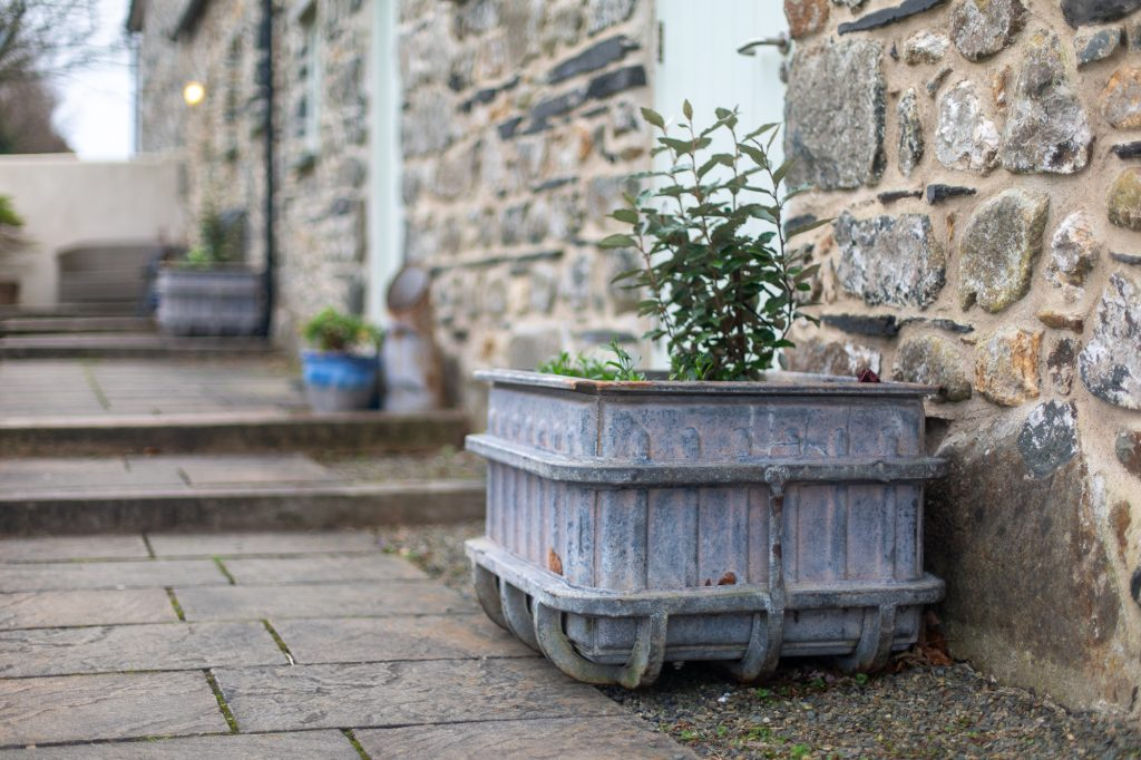 YR Hafan holiday cottages - barn conversions with ammunition boxes as planters