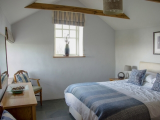 Yr Hafan- Penberi Self Catering Cottage bedroom  with sea views from king size bed