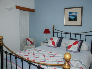 Pencaer Self Catering Cottage -pretty bedroom with kingsize bed and sea views